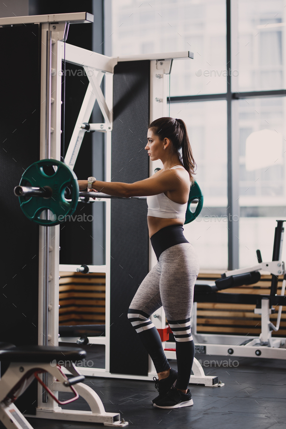 Athletic girl dressed in sportswear is going to lift weight in the modern gym - Stock Photo - Images