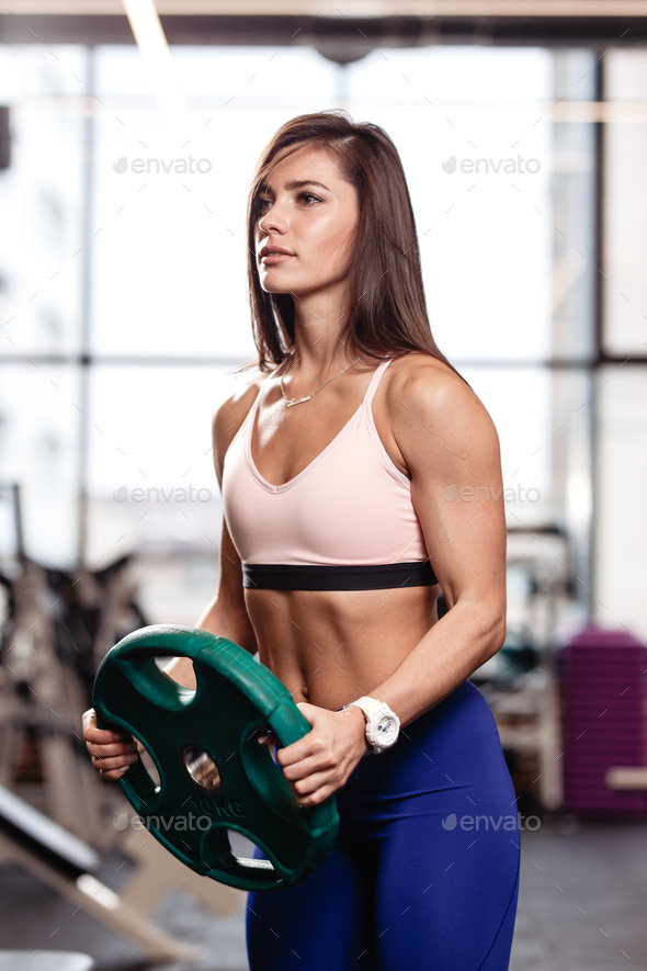 Athletic young brunette girl holds a heavy plate in her hands in the modern gym - Stock Photo - Images