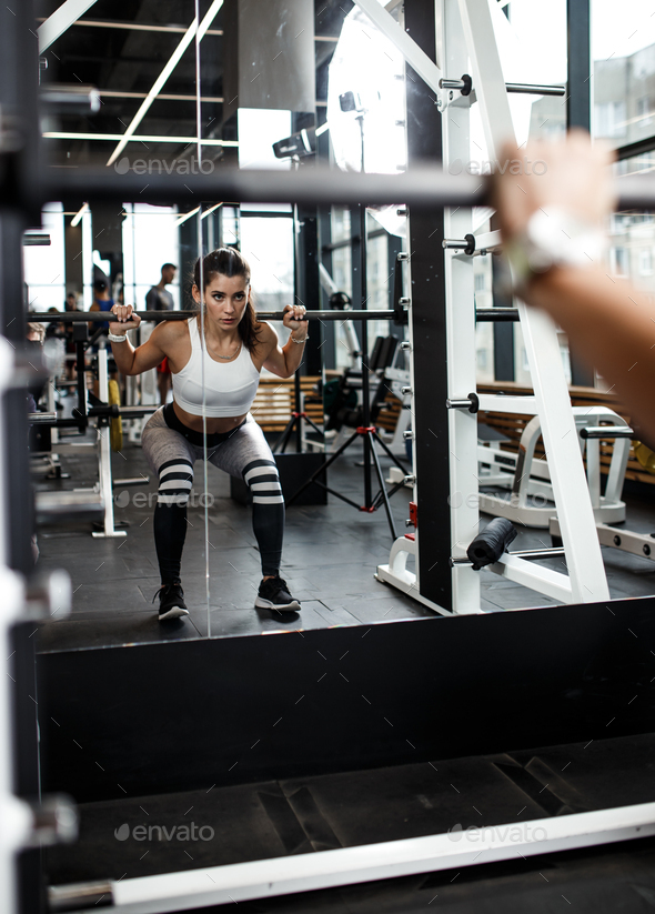 Young athletic girl dressed in sportswear squats with a barbell in front of the mirror in the modern - Stock Photo - Images