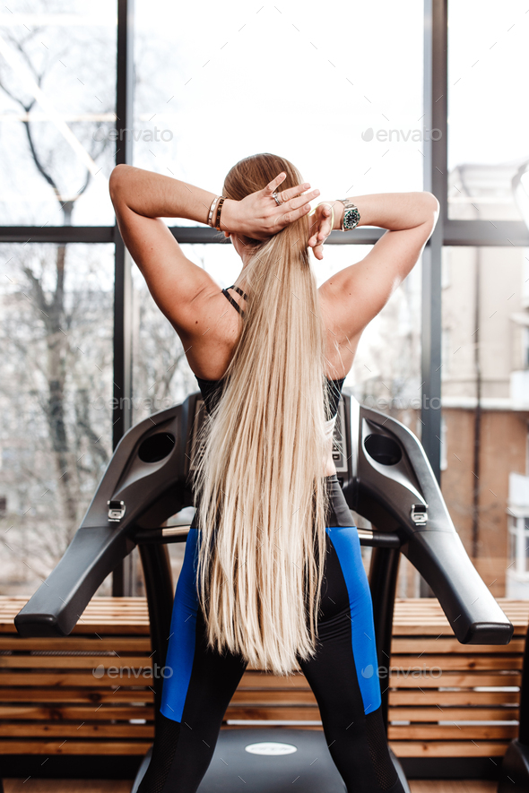 The athletic girl with long blond hair dressed in a sportswear is standing on the treadmill in front - Stock Photo - Images