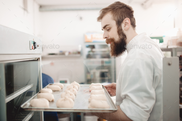 Young charismatic baker puts a baking tray with breads rolls in the oven in the bakery - Stock Photo - Images