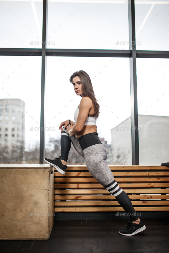 Athletic young brunet girl dressed in sportswear is doing stretching next to the wooden windowsill - Stock Photo - Images
