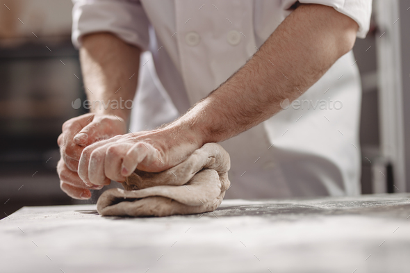 Baker kneads dough on the table in the bakery - Stock Photo - Images