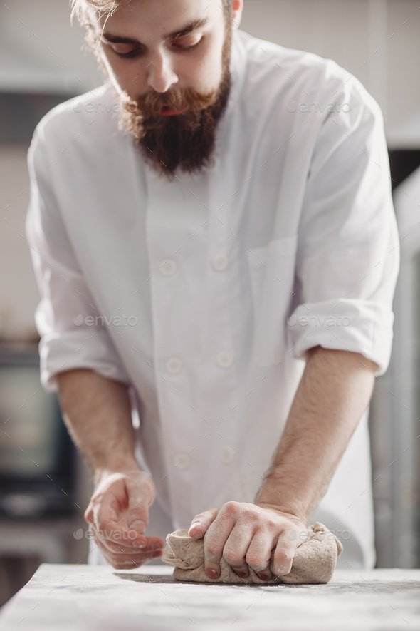 Charismatic baker with a beard and mustache kneads dough on the table in the bakery - Stock Photo - Images