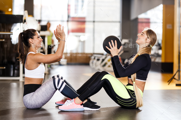 Two young athletic girls dressed in sportswear are doing together sport exercises for press with - Stock Photo - Images