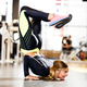 Young athletic girl dressed in sportswear doing handstand on the floor in the modern gym - PhotoDune Item for Sale