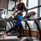 The athletic girl dressed in a sportswear is running on the treadmill in front of the windows in the - PhotoDune Item for Sale