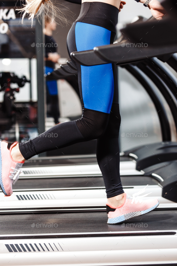 The athletic girl dressed in a sportswear is running on the treadmill in front of the windows in the - Stock Photo - Images