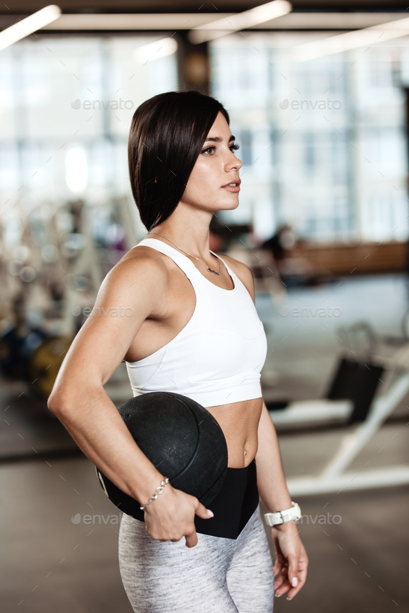 Slender brunette girl dressed in a sportswear is standing with heavy fitness ball in her hands in - Stock Photo - Images