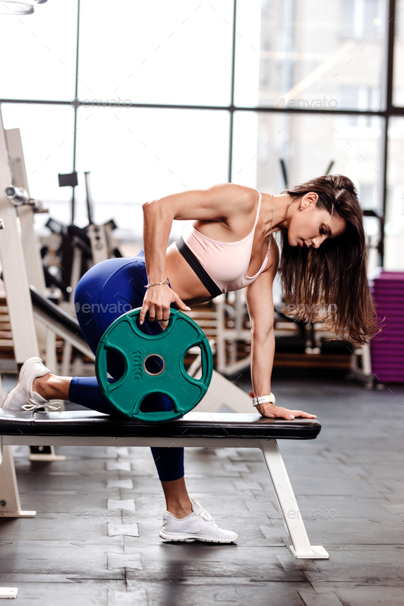 Young ahletic brunette girl dressed in a sportswear is doing exercises for back with plate on the - Stock Photo - Images
