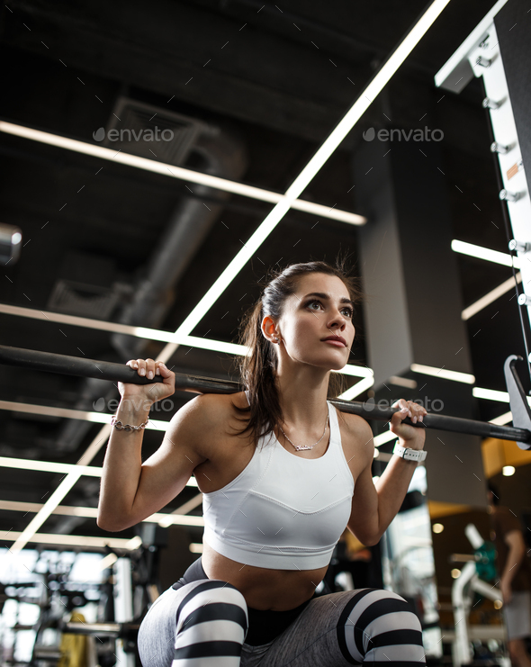 Athletic young girl dressed in sportswear squats with a barbell in the modern gym - Stock Photo - Images