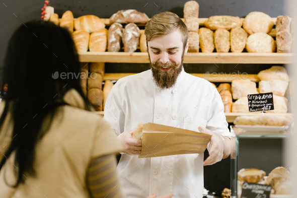 Charismatic baker with a beard and mustache gives a paper bag of bread to the customer in the bakery - Stock Photo - Images