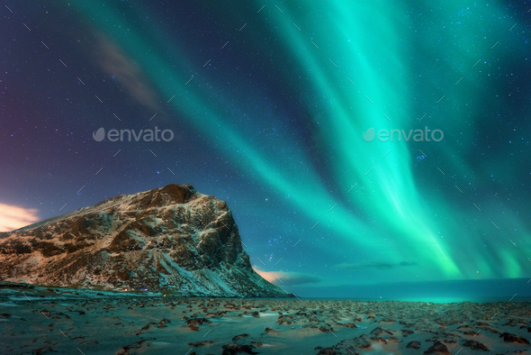 Aurora borealis above the snowy mountains and sandy beach - Stock Photo - Images