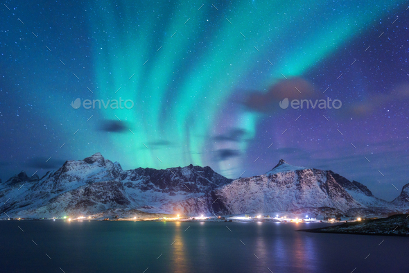 Aurora borealis over the sea, snowy mountains and city lights - Stock Photo - Images