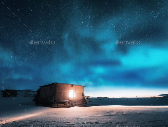 Aurora borealis over old small house with yellow light in window - Stock Photo - Images