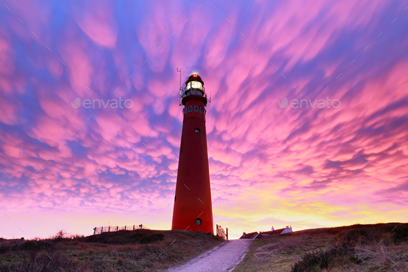 spectacular purple mammatus clouds over red lighthouse - Stock Photo - Images