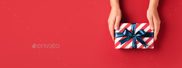 Red Banner with Female's Hands Holding Striped Gift Box. - Stock Photo - Images