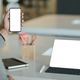 Young businessman hold a blank screen smartphone in hand and a blank screen laptop on the desk. - PhotoDune Item for Sale