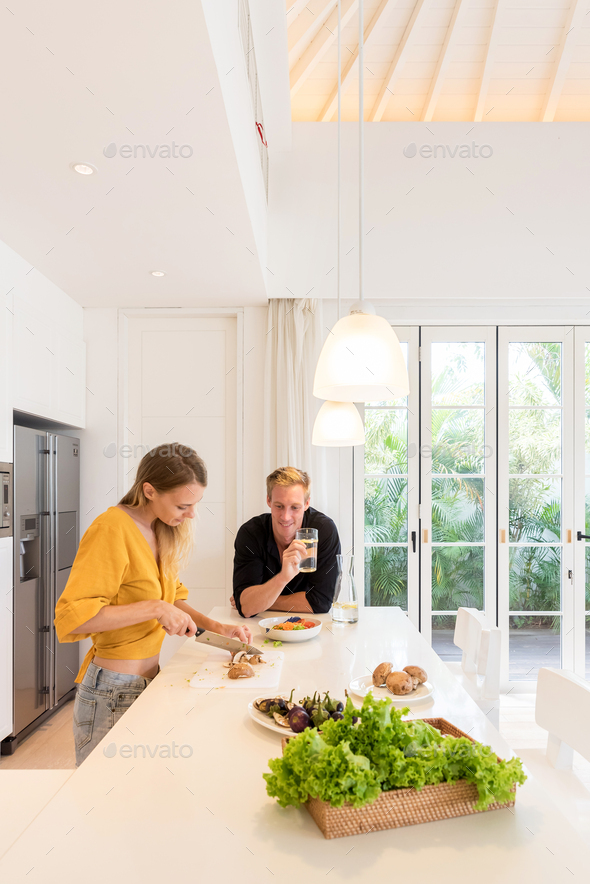 Couple making lunch on a white kitchen at home - Stock Photo - Images