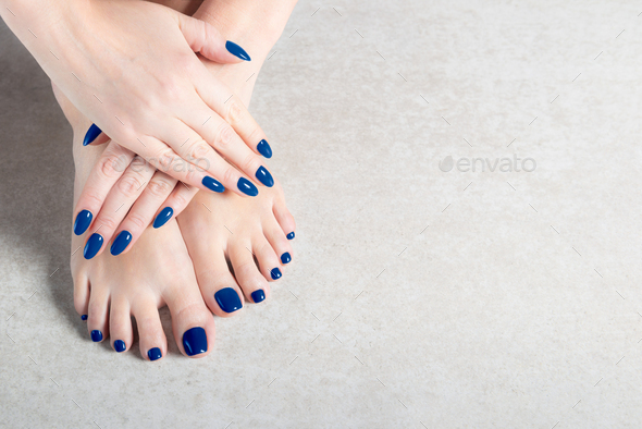 Young lady is showing her blue manicure and pedicure nails - Stock Photo - Images