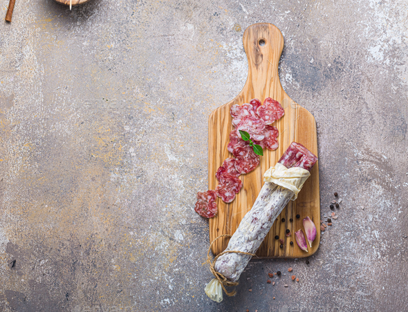 Italian salami on wooden board with cheese and olives - Stock Photo - Images