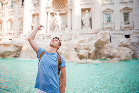 Happy man tourist trowing coins at Trevi Fountain, Rome, Italy for good luck. Caucasian guy making a - Stock Photo - Images