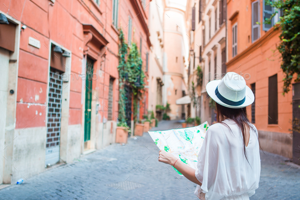 Happy young woman with a city map on desert street in Europe. Travel tourist woman with map in Rome - Stock Photo - Images