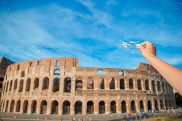 Closeup toy airplane on Colosseum background. Italian european vacation in Rome. Concept of travel - Stock Photo - Images