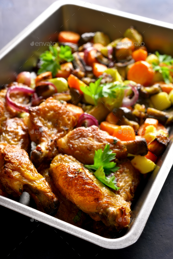 Baked chicken wings with vegetables in baking tray - Stock Photo - Images