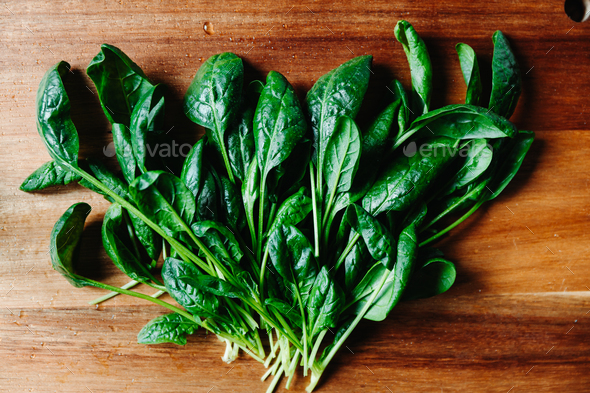 Top view of fresh spinach leaves on a wooden cutting board - Stock Photo - Images