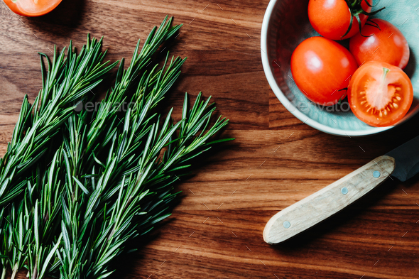 Lifestyle photo of cooking healthy eating with tomatoes and fresh rosemary - Stock Photo - Images