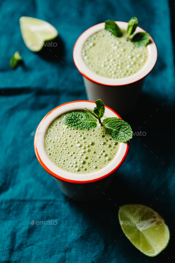 Two portions of green spinach smoothie with banana, lime and plant milk. - Stock Photo - Images