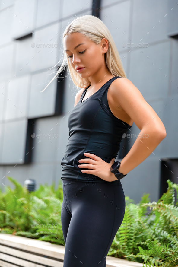 Confident fit young woman rests with hands on her hips and smiling - Stock Photo - Images