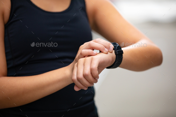 Close-up of woman using fitness smart watch device after running - Stock Photo - Images