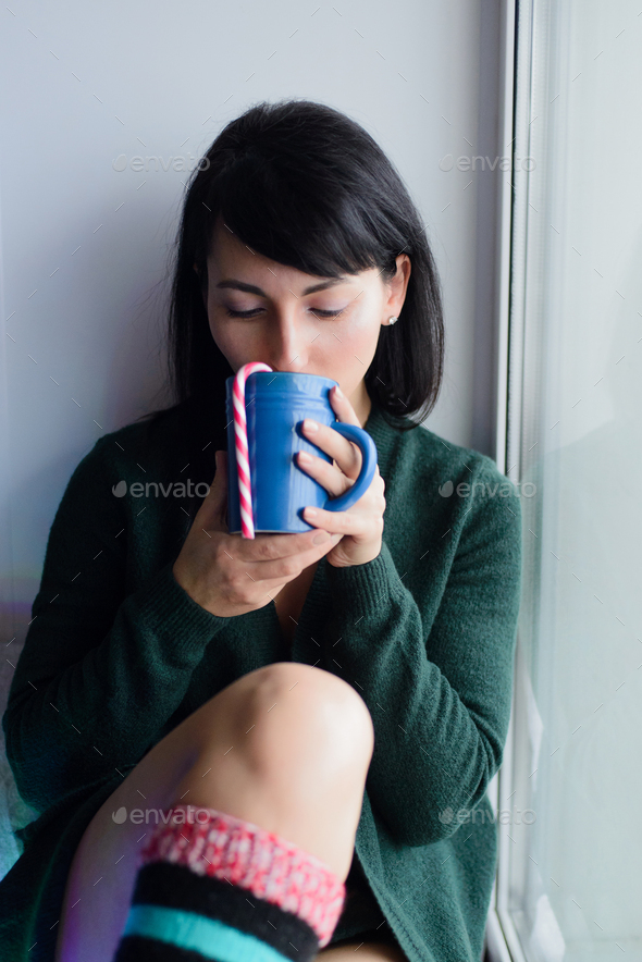 woman on windowsill with beverage and striped candy cane - Stock Photo - Images