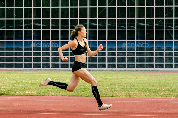 female athlete in spikes shoes running - Stock Photo - Images