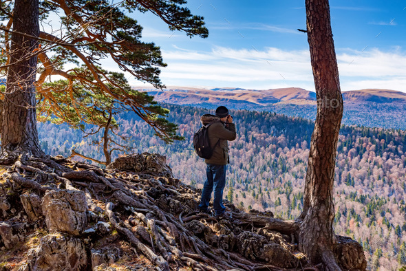 Male hiker takes photo of beautiful mountains in autumn. North Caucasus - Stock Photo - Images