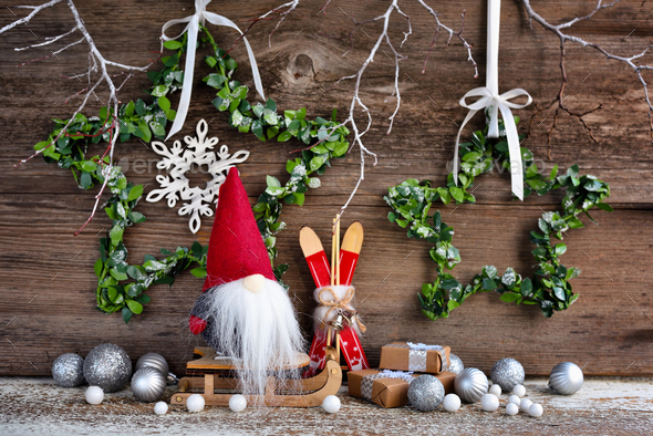 Christmas composition with a gnome on sleigh and festive decorations - Stock Photo - Images