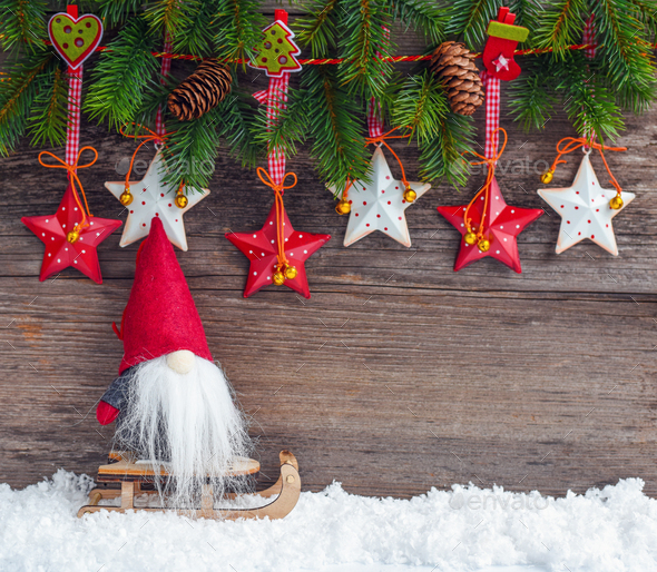 Christmas stars with a gnome on a sleigh and branches of spruce on wooden background - Stock Photo - Images