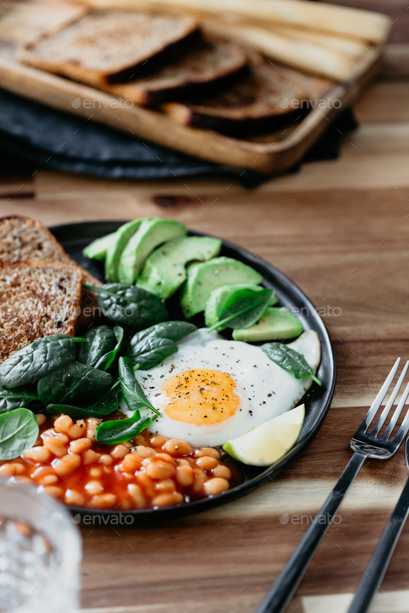 Healthy breakfast with fried egg, avocado, toasts, beans and fresh spinach - Stock Photo - Images