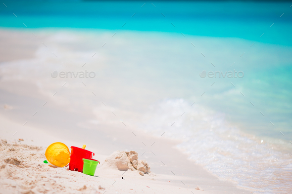 Kids beach toys on white sandy beach background turquiose water - Stock Photo - Images