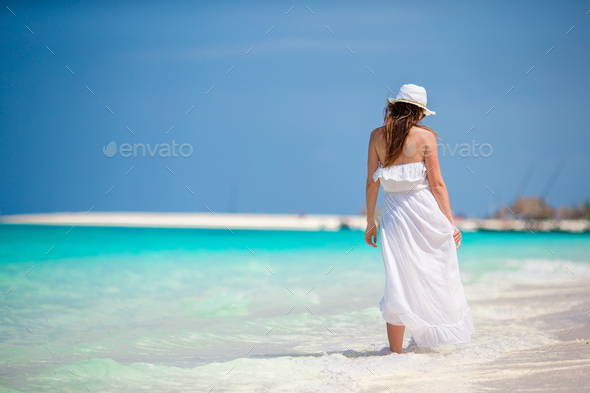 Young beautiful woman during tropical beach vacation. Enjoy summer vacation alone on the beach with - Stock Photo - Images