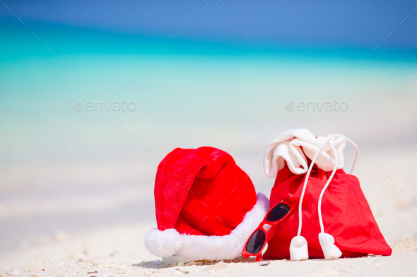 Closeup of red Santa bag and Santa Claus hat on beach. Xmas travel vacation and travel cuprise - Stock Photo - Images