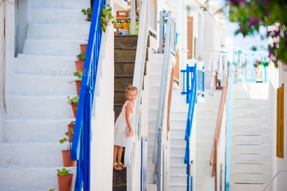 Cute girl in blue dress at street of typical greek traditional village with amazing steps, white - Stock Photo - Images