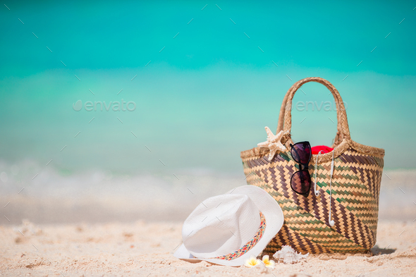 Straw bag, fist star, headphones, hat and sunglasses on white beach - Stock Photo - Images