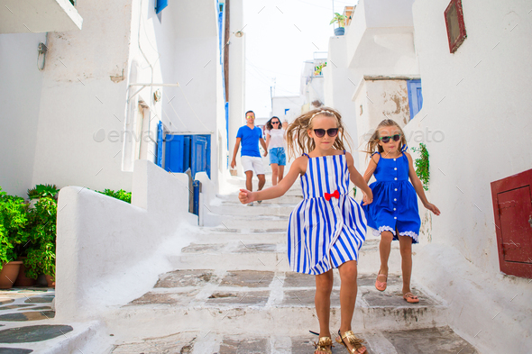 Family vacation in Europe. Parents and kids at street of typical greek traditional village on - Stock Photo - Images