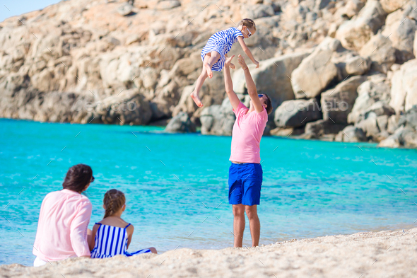 Young family having fun on the beach - Stock Photo - Images