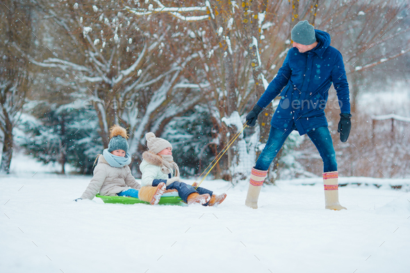 Little girls enjoying sledding in winter day. Father sledding his little adorable daughters. Family - Stock Photo - Images