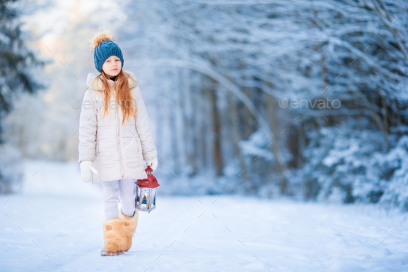 Little girl with latern in frozen forest on Christmas eve - Stock Photo - Images
