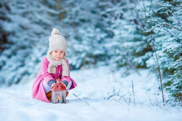Adorable little girl wearing warm coat outdoors on Christmas day warms cold hands by flashlight - Stock Photo - Images